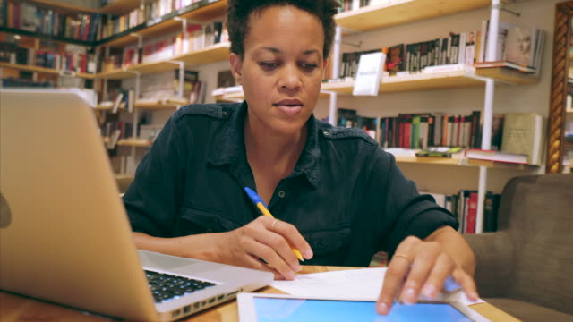 Woman studying. Woman in a bookstore or library studying for a new project. She is using a laptop, digital tablet and some papers for notes. adult stock videos & royalty-free footage