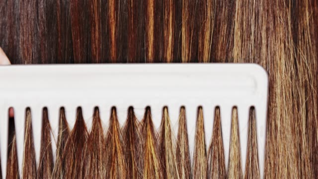 Woman styling her long hair with comb Young woman styling her long straight shiny dyed hair with comb, visible color layers highlights, care concept highlights hair stock videos & royalty-free footage