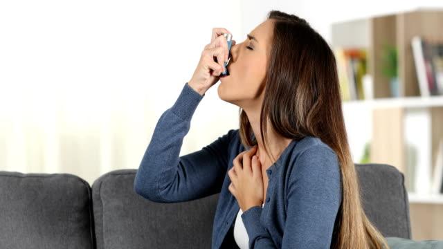 Woman suffering asthma attack using inhaler video