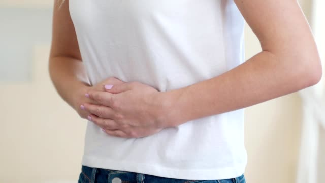 Woman suffering from abdominal pain at home Woman suffering from abdominal pain at home. gripping stock videos & royalty-free footage