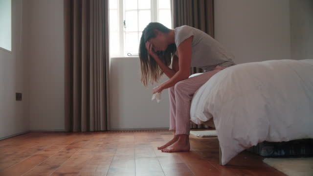 Woman Suffering From Depression Sitting On Bed In Pajamas video