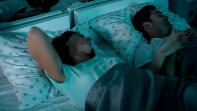 Woman suffering from insomnia Young woman can't sleep so she is rolling in bed late at night. Husband sleeps peacefully next to her. insomnia stock videos & royalty-free footage