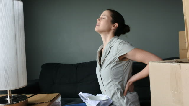 Woman suffers from back pain due to unpacking boxes video