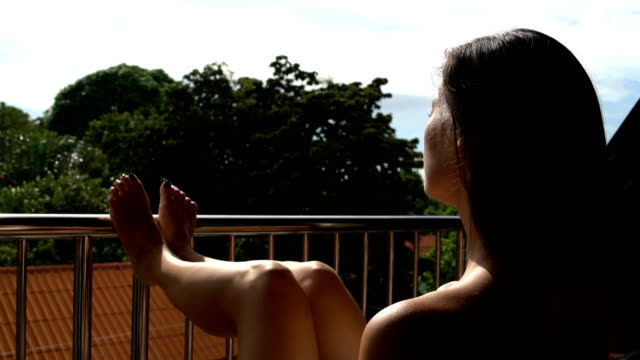 A woman sunbathes on the hotel balcony Woman sunbathing on the hotel balcony sunbathing stock videos & royalty-free footage