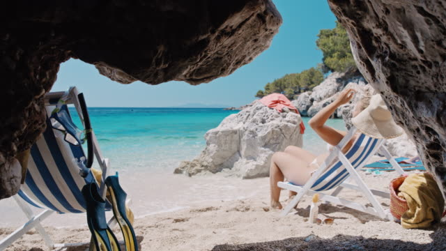 SLO MO Woman sunbathing on an idyllic remote beach Slow motion shot of a woman sunbathing on an idyllic remote beach. Croatia. Shoot in 8K resolution one mid adult woman only stock videos & royalty-free footage