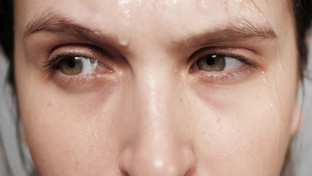 woman sweat flows down his face with drops, girl is nervous and afraid to look around. paranoia, isolation, self-isolation, quarantine, panic, fear, mental stress concept. close-up - sudore video stock e b–roll