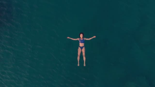 AERIAL SLOW MOTION: woman swimming in blue transparent sea AERIAL SLOW MOTION: woman floating on blue water surface, swimming in transparent mediterranean sea, top down view, summer vacation concept floating on water stock videos & royalty-free footage