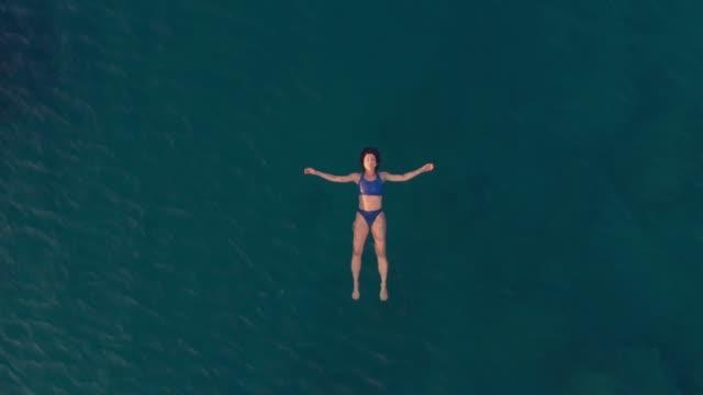 vídeos de stock, filmes e b-roll de antena lenta: mulher nadando no mar azul transparente - flutuando na água