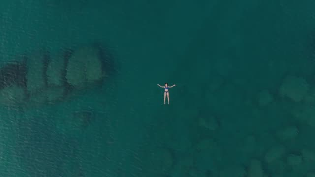 AERIAL: woman swimming in blue transparent sea AERIAL: woman floating on blue water surface, swimming in transparent mediterranean sea, top down view, summer vacation concept floating on water stock videos & royalty-free footage