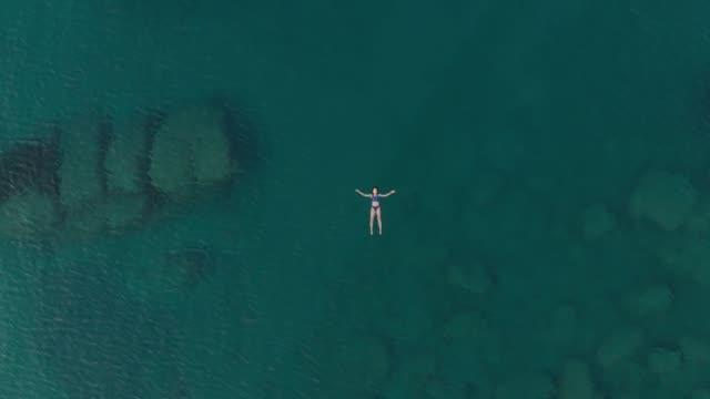 vídeos de stock, filmes e b-roll de antena: mulher nadando no mar azul transparente - flutuando na água