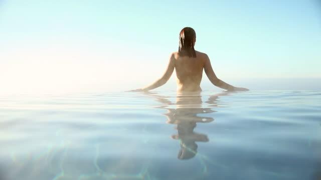 Woman swimming in infinity pool overlooking ocean video
