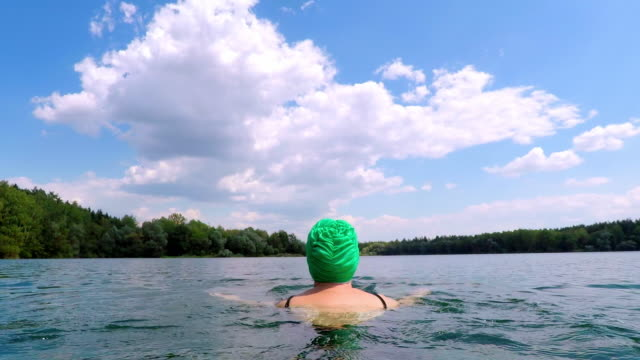 vídeos de stock e filmes b-roll de woman swimming in lake with swimming cap - margem do lago