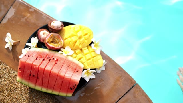 4K woman swimming in pool eating tropical fruit