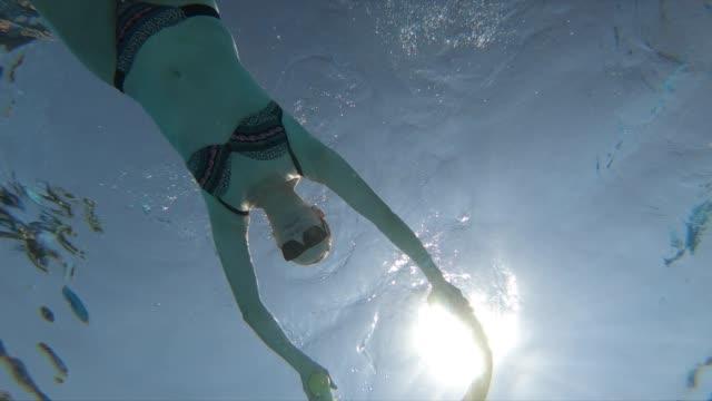 vidéos et rushes de femme nageant sous l'eau dans la piscine de ressource - vue en contre plongée verticale