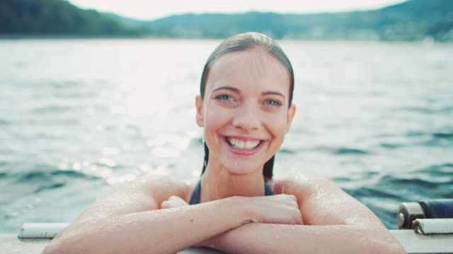Woman swimming A young woman swimming in a lake.   swimming stock videos & royalty-free footage