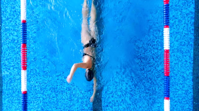 A woman swims in crawl in an open back swimsuit. A professional swimmer in an athletic swimsuit, a cap and goggles swims in craw. swimming stock videos & royalty-free footage