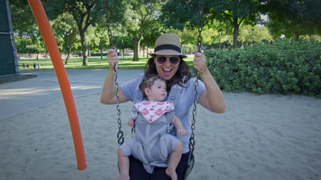 Woman swinging on a swing with baby on carrier at playground video