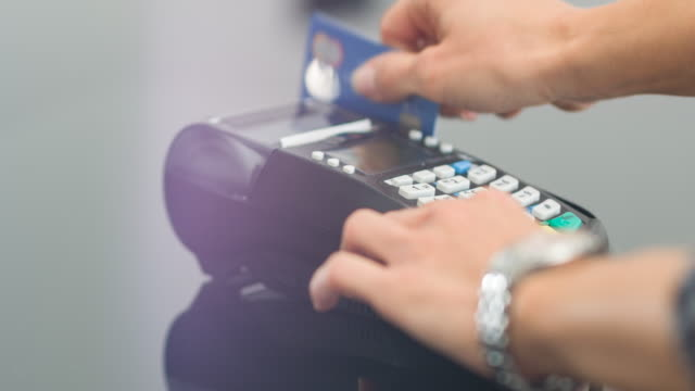 Woman swiping credit card and entering PIN code Woman making a purchase by sliding credit card at point of sale terminal and entering PIN code credit card purchase stock videos & royalty-free footage