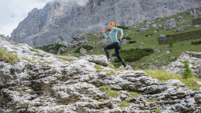 kvinnan svans kör, lämnar bakom vägar och spår, och beger sig på dramatiska bergsvägar - jogging hill bildbanksvideor och videomaterial från bakom kulisserna