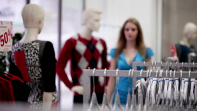 Woman take a dress from hanger in clothing store video