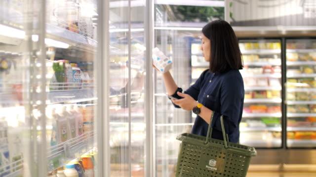 Woman take a fresh milk in supermarket , slow motion