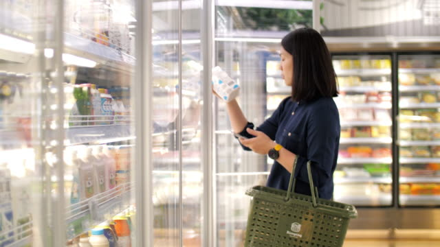 vídeos de stock e filmes b-roll de woman take a fresh milk in supermarket , slow motion - store