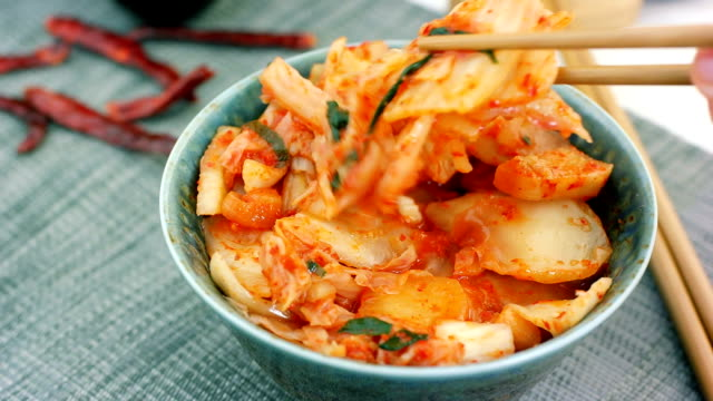 Woman take traditional korean cabbage appetizer Kimchi from bowl with chopsticks video