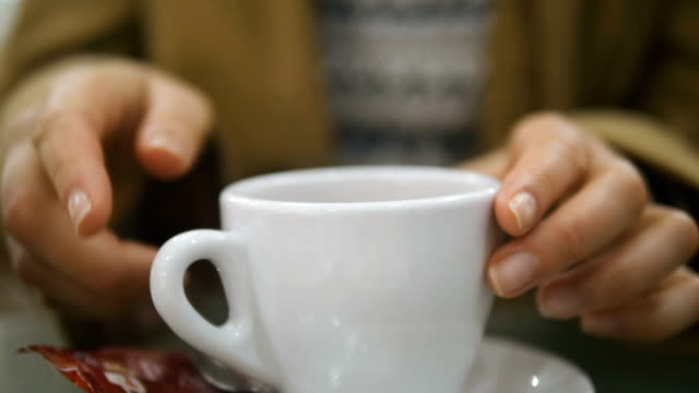 woman takes a cup of coffee with a saucer closeup