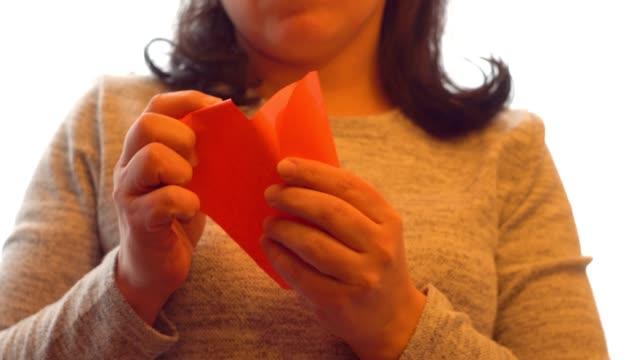 A woman takes a paper heart