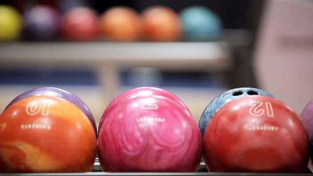 Woman takes bowling ball. Close up video