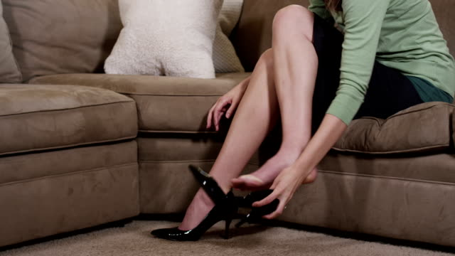 Woman takes of high heel shoes and massages feet video