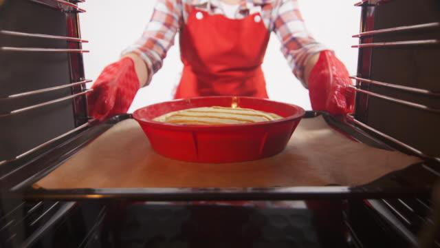 女人拿出烤盤從烤箱裡煮熟的南瓜餅 - pumpkin pie 個影片檔及 b 捲影像