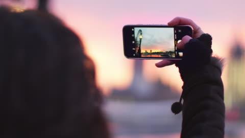 vídeos de stock e filmes b-roll de woman takes photo of big ben on mobile phone at sunset - fotografia imagem