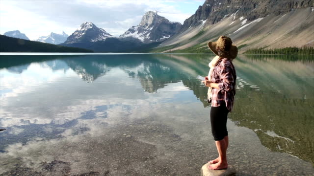 Woman takes picture of mountain lake video