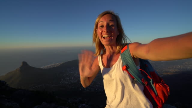 Woman takes selfie portrait on top of Table Mountain, Cape Town Young woman in Cape Town takes selfie portrait from Table Mountain top table mountain national park stock videos & royalty-free footage