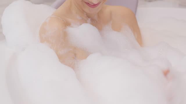 kvinna tar ett bubbelbad i badrummet. hon städar sig med glada känslor. - japanese bath woman bildbanksvideor och videomaterial från bakom kulisserna