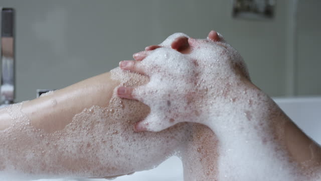 Woman taking a bubble bath showing her legs and feet out of the water - Vidéo