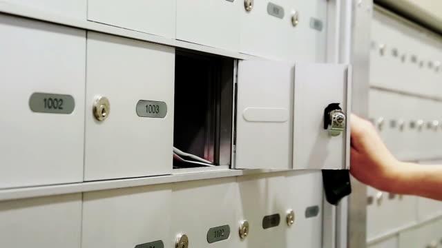 frau nimmt ein e-mail von ihren briefkasten - briefkasten stock-videos und b-roll-filmmaterial