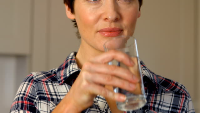 A woman taking a pill video