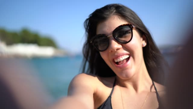 Woman taking a selfie during vacations in a beautiful beach