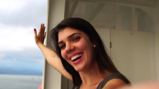 woman taking a selfie from a cruise ship - paesaggio marino video stock e b–roll
