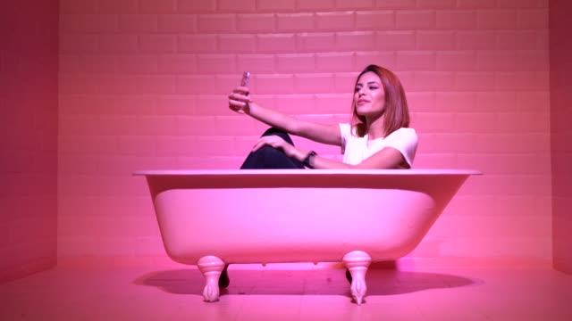 Woman Taking a Selfie in the pink bathtube