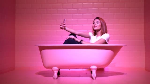 여자는 selfie 핑크 bathtube에서 복용 - influencer 스톡 비디오 및 b-롤 화면