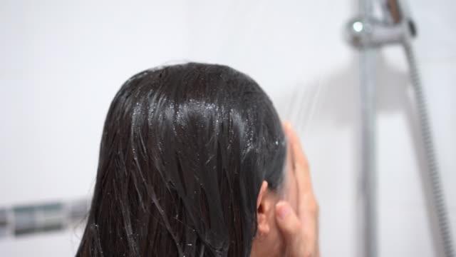 vidéos et rushes de femme prenant une douche. - soins capillaires