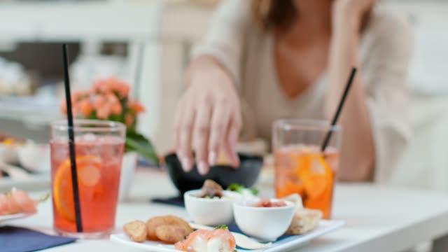 vídeos de stock, filmes e b-roll de mulher tomando aperitivo finger food durante coquetel aperitivo no café da cidade. tiro de detalhe próximo. viagem italiana de amigos na úmbria.4k câmera lenta - antepasto