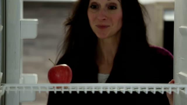 woman taking apple from fridge video
