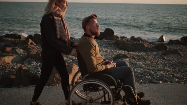 Woman taking care of disabled husband and walking with him by the sea - vídeo