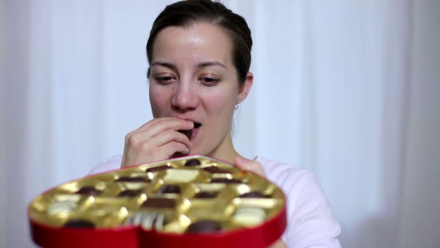 Woman taking chocolate from heart shaped box