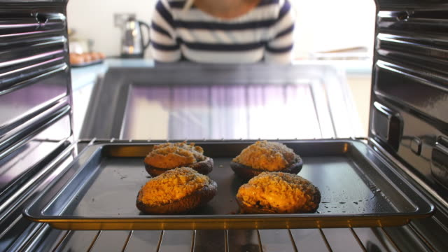 Woman Taking Cooked Stuffed Mushrooms Out Of The Oven Woman opens door of oven and takes out tray of cooked stuffed mushrooms. Shot on Sony FS700 at a frame rate of 25 fps stuffed stock videos & royalty-free footage