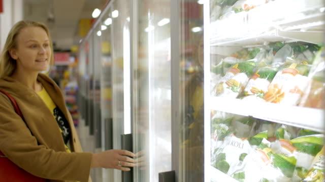 Woman taking frozen product in the shop fridge video